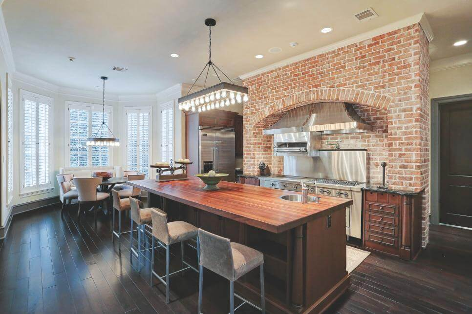 Chef Kitchen With Barstools and Brick Wall